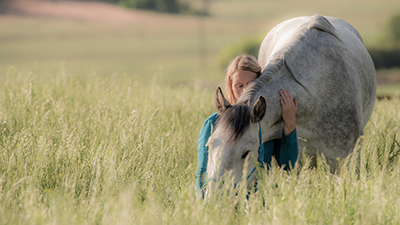 A woman patting a horse in a tall grassy field